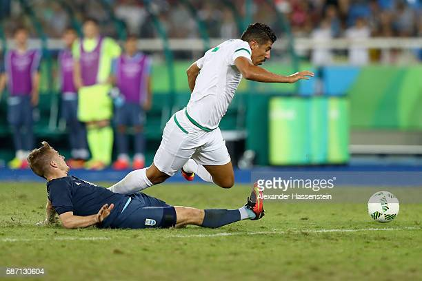 Santiago Ascacibar of Argentina battles for the ball with Baghdad Bounadjah of Algeria during the Men's Group D first round match between Argentina...