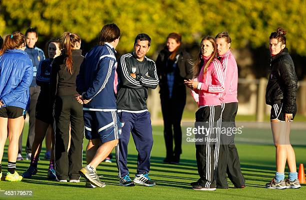 Santiago Capurro coach of Las Leonas talks with his players on the field after a press conference to announce modifications in the support staff of...