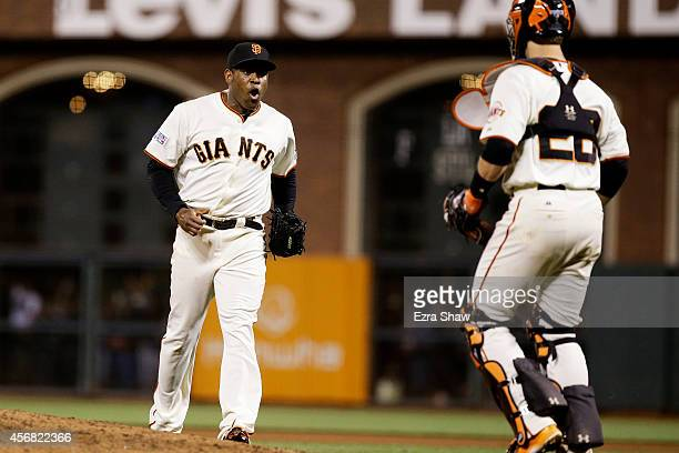 Santiago Casilla and Buster Posey of the San Francisco Giants celebrate after the final out of their 3 to 2 win over the Washington Nationals during...
