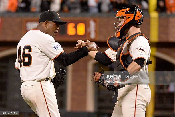 Santiago Casilla and Buster Posey of the San Francisco Giants celebrate after getting the final out in the ninth inning against the St Louis...