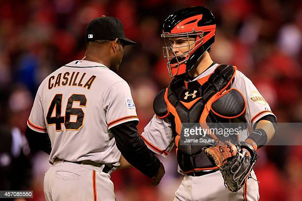 Santiago Casilla and Buster Posey of the San Francisco Giants celebrate their 3 to 0 win over the St Louis Cardinals in Game One of the National...