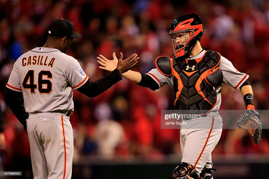 Santiago Casilla #46 and Buster Posey #28 of the San Francisco Giants celebrate their 3 to 0 win over the St. Louis Cardinals in Game One of the National League Championship Series at Busch Stadium on October 11, 2014 in St Louis, Missouri.