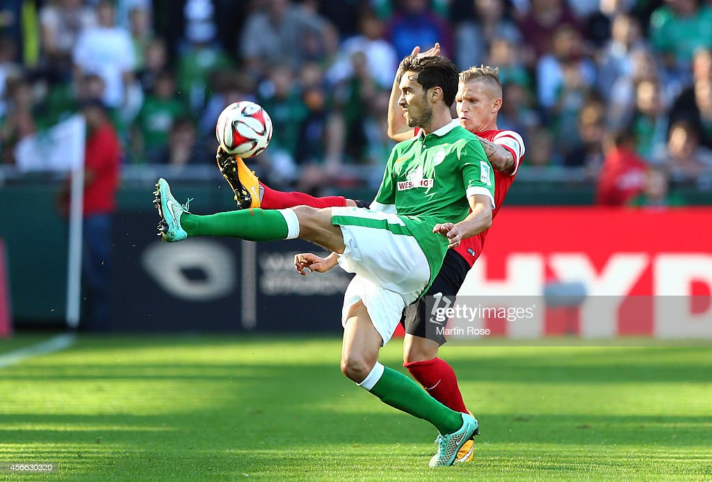 Santiago Garcia of Bremen and Jonathan Schmid of Freiburg battle for the ball during the Bundesliga match between SV Werder Bremen and SC Freiburg at...