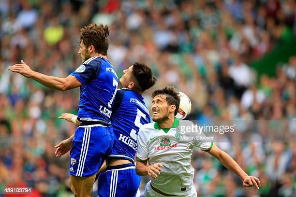 Santiago Garcia of Bremen challenges Benjamin Huebner and Mathew Leckie of Ingolstadt during the Bundesliga match between Werder Bremen and FC...