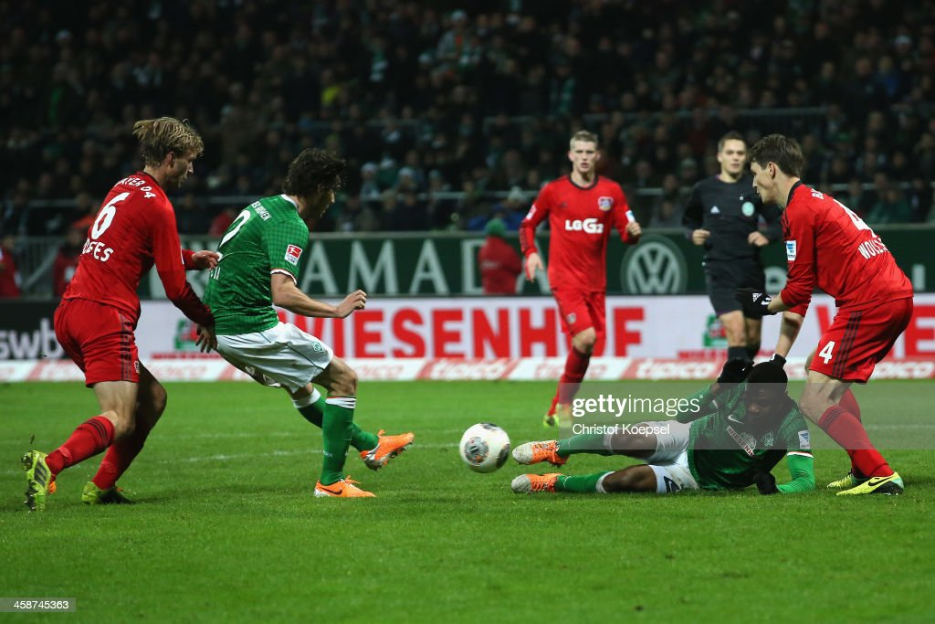Santiago Garcia of Bremen (2nd L) scores the first goal against <a gi-track='captionPersonalityLinkClicked' href=/galleries/search?phrase=Simon+Rolfes&family=editorial&specificpeople=635100 ng-click='$event.stopPropagation()'>Simon Rolfes</a> of Leverkusen (L) and Phillipp Wollscheid of Leverkusen (R) during the Bundesliga match between Werder Bremen and Bayer Leverkusen at Weserstadion on December 21, 2013 in Bremen, Germany.
