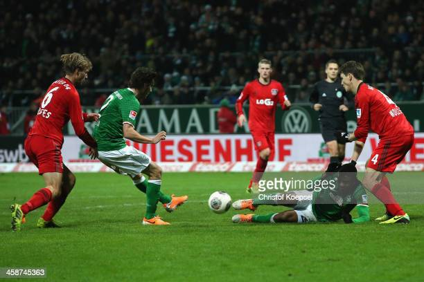 Santiago Garcia of Bremen scores the first goal against Simon Rolfes of Leverkusen and Phillipp Wollscheid of Leverkusen during the Bundesliga match...