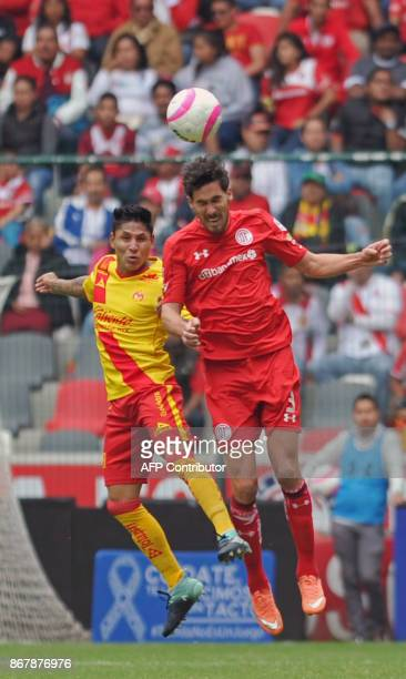 Santiago Garcia of Toluca jumps for a header with Morelia's Peruvian player Raul Ruidiaz during their Mexican Apertura tournament football match at...