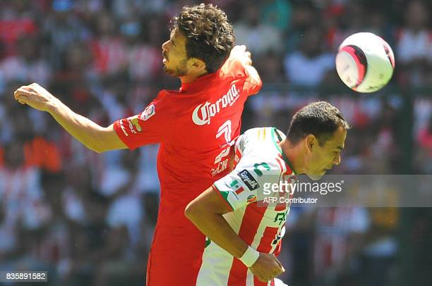 Santiago Garcia of Toluca jumps for the ball with Pablo Velazquez of Necaxa during their Mexican Apertura football tournament match at the Nemesio...