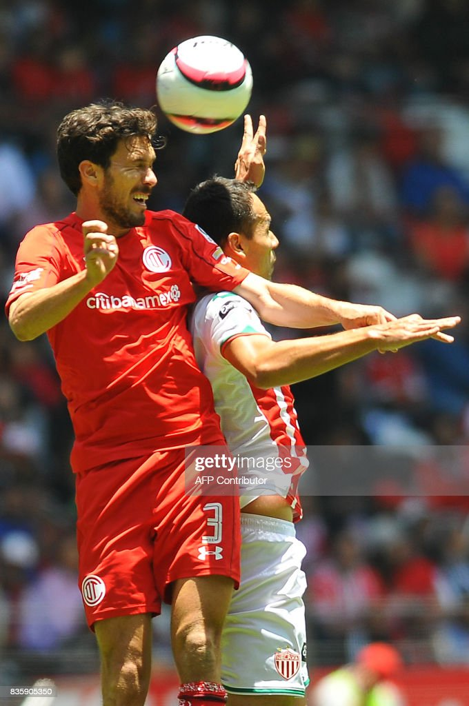 Santiago Garcia (L) of Toluca jumps for the ball with Pablo Velazquez of Necaxa during their Mexican Apertura football tournament match at the Nemesio Diez stadium in Toluca, Mexico, on August 20, 2017. /