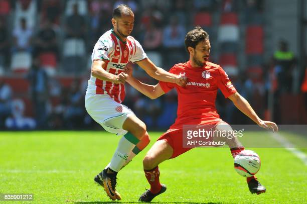 Santiago Garcia of Toluca vies for the ball with Carlos Gonzalez of Necaxa during their Mexican Apertura football tournament match at the Nemesio...