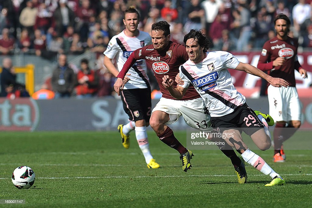 Santiago Garcia (R) of US Citta di Palermo is challenged by Matteo Brighi of Torino FC during the Serie A match between Torino FC and US Citta di Palermo at Stadio Olimpico di Torino on March 3, 2013 in Turin, Italy.