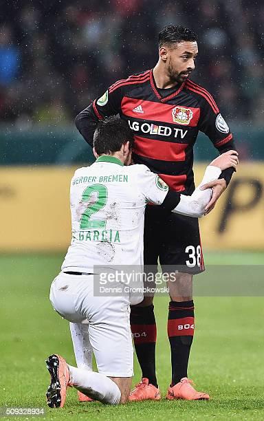 Santiago Garcia of Werder Bremen is assisted by Karim Bellarabi of Bayer Leverkusen during the DFB Cup Quarter Final match between Bayer Leverkusen...