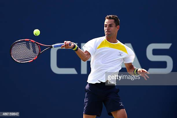 Santiago Giraldo of Colombia returns a shot against Austin Krajicek of the United States during during their Men's Singles First Round match on Day...
