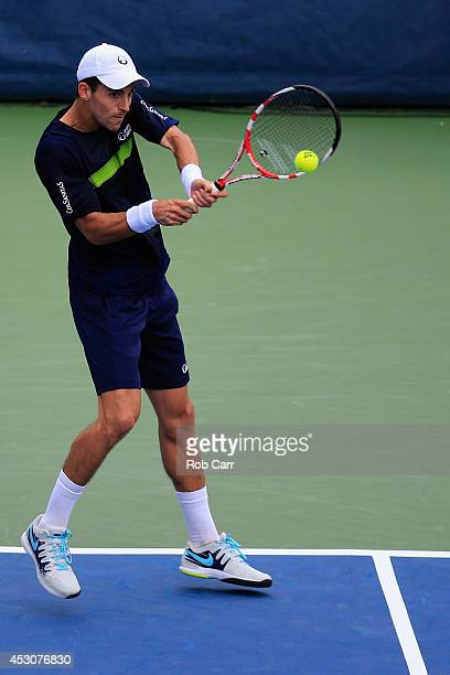 Santiago Giraldo of Colombia returns a shot to Vasek Pospisil of Canada during the Citi Open at the William HG FitzGerald Tennis on August 2 2014 in...