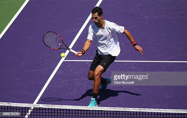 Santiago Giraldo of Columbia plays a forehand volley against Andy Murray of Great Britain in their third round match during the Miami Open Presented...