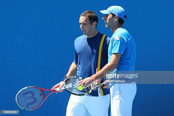 Santiago Gonzalez of Mexico and Scott Lipsky of the United States talk tactics in their men's doubles first round match against Paul Hanley of...