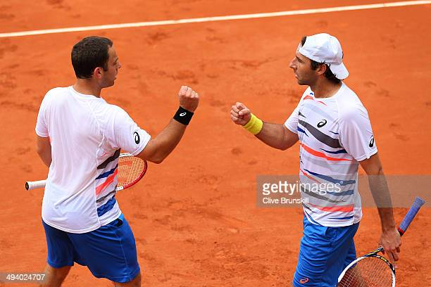 Santiago Gonzalez of Mexico and Scott Lipsky of the United States bump fists during their men's doubles match against Ross Hutchins and Colin Fleming...