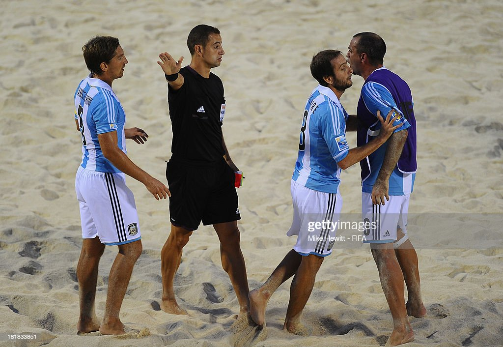 Santiago Hilaire of Argentina is restrained by team mate Federico Hilaire after being sent off by referee Ruben Eiriz during the FIFA Beach Soccer World Cup Tahiti 2013 Quarter Final match between Argentina and Tahiti at the Tahua To'ata Stadium on September 25, 2013 in Papeete, French Polynesia.