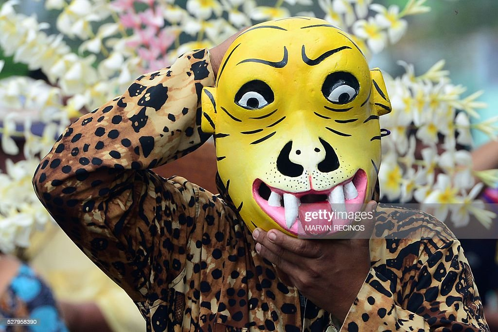 A masked performer takes part in a ceremony in honor of the day of the Holy Cross in Santiago Nonualco, 48 km south from San Salvador, on May 3, 2016. The inhabitants of Santiago Nonualco offer fruits to the Holy Cross in gratitude for the harvest obtained in the year and by the beginning of the rainy season. / AFP / MARVIN