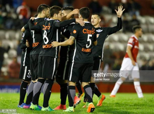 Santiago Salcedo of Libertad celebrates with teammates Juan Danilo Santacruz and Ivan Ramirez after scoring the fifth goal of his team during a first...