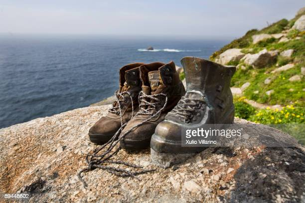 Santiago's Way Jacobean Routes French way Finisterra's extension A pair of pilgrim's boots set by the side on a bronze sculpture of a boot which...