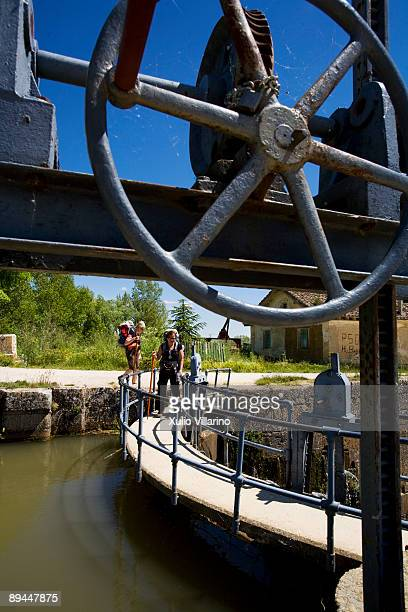 Santiago's Way Jacobean Routes French Way Two pilgrim women walking along the Castilla Channel lock placed at the entrance of Fromista Palencia This...