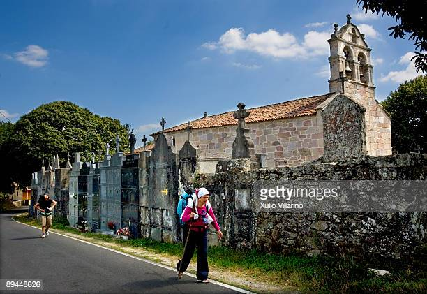 Santiago's Way Jacobean Routes French way Two pilgrims with their rucksacks and walking sticks walk along the road which is by the cementery and the...