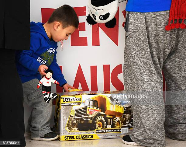Santino Martinez grabs his newly acquired Tonka toy truck at the 86th annual Denver Santa Claus Shop at the old Kmart store near Evans Ave and Monaco...