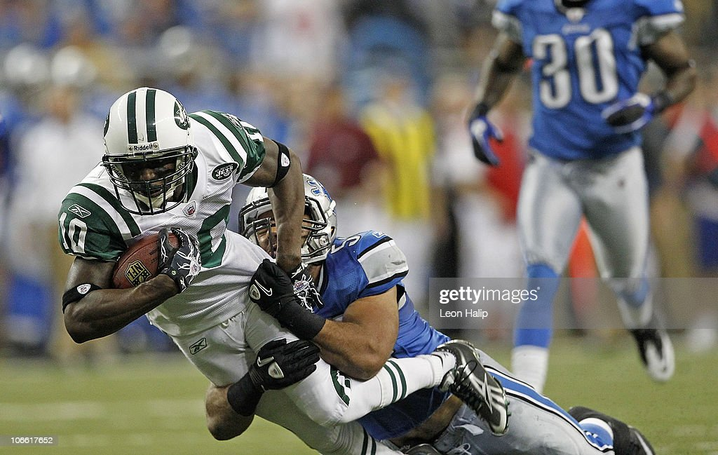 Santonio Holmes #10 of the New York Jets catches a 54 yard pass in overtime and is tackled by Landon Johnson #54 of the Detroit Lions during the overtime period at Ford Field on November 7, 2010 in Detroit, Michigan. The Jets defeated the Lions 23-20 in overtime.