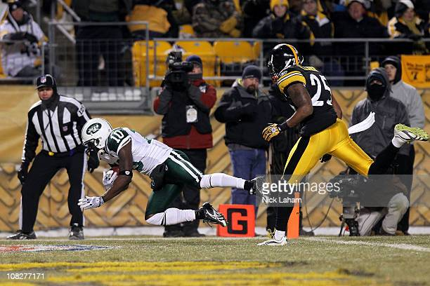 Santonio Holmes of the New York Jets scores a third quarter touchdown in front of Ryan Clark of the Pittsburgh Steelers during the 2011 AFC...