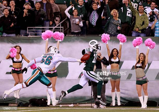 Santonio Holmes of the New York Jets scores a touchdown in the fourth quarter against Kevin Burnett of the Miami Dolphins at MetLife Stadium on...
