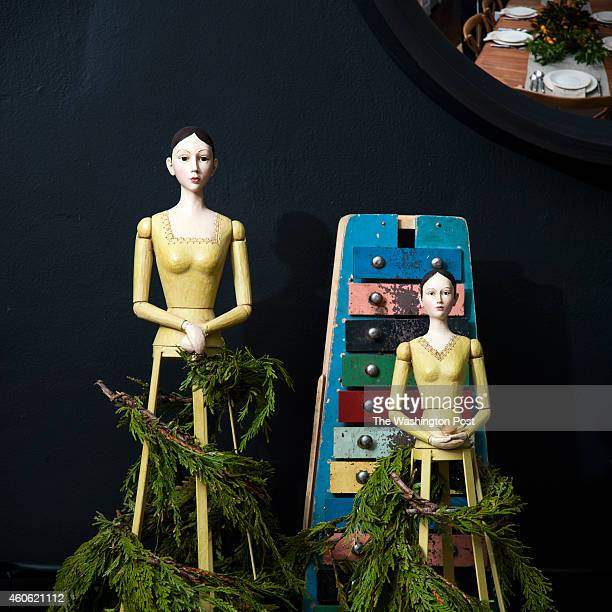 Santos cage dolls are draped with greenery for a festive flair to a roll cart used as a gin bar in the dining room of Mark and Hallie Burrier...