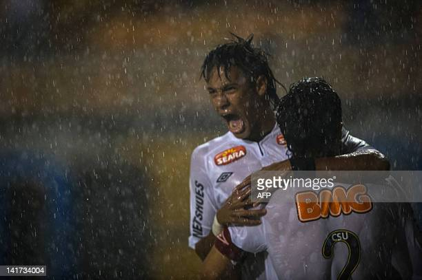 Santos' Neymar and Edu Dracena celebrate the latter's goal against Peru's Juan Aurich during their Copa Libertadores football match at Pacaembu...