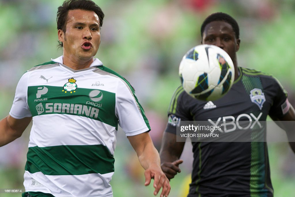 Santos's Aaron Galindo (L) disputes the ball with Eddy Johnson (R) of Seattle Sounder during their CONCACAF Champions League first leg semi-final match in Torreón, Coahuila state on April 9, 2013.