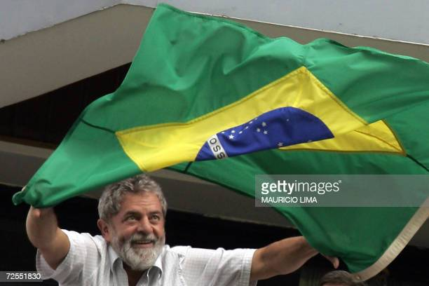 Brazil's presidential candidate for reelection Luiz Inacio Lula da Silva of the Workers' Party waves a national flag to supporters from the balcony...