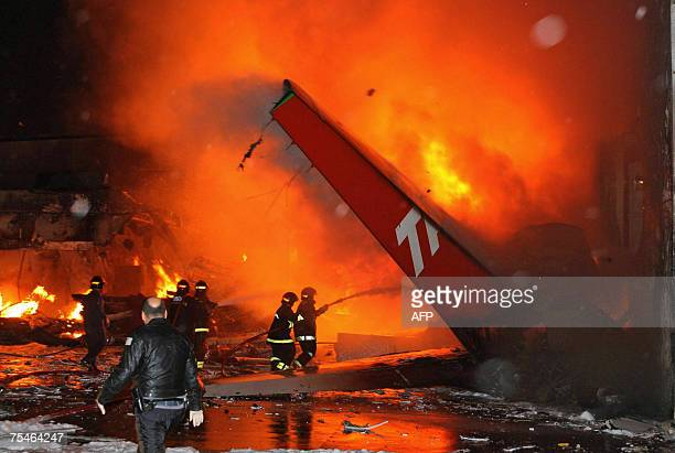 Firefighters try to extiguish the fire around the wreckage of a TAM Brazilian airlines A320 passenger aircraft that crashed 17 July 2007 while...
