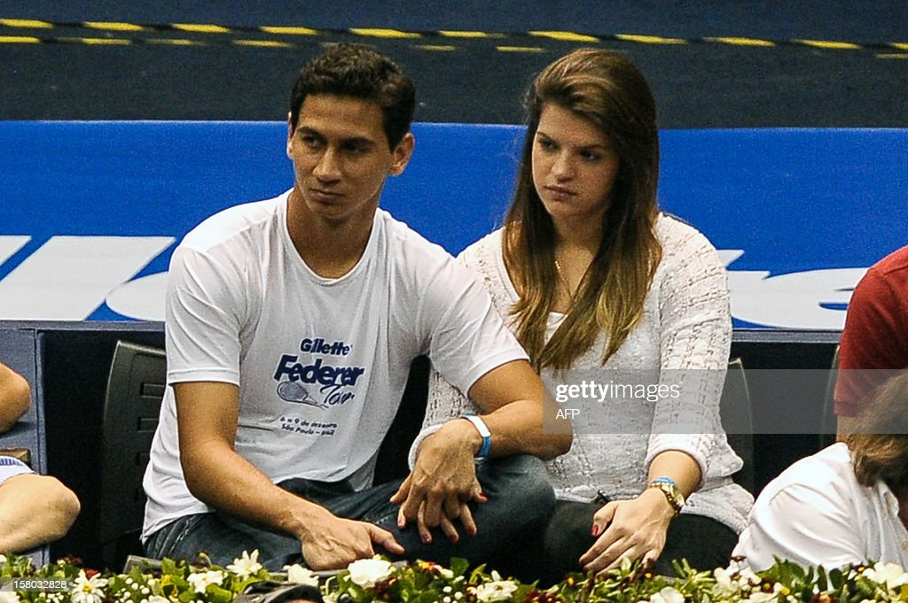 Sao Paulo's football player Ganso (L) watches the exhibition tennis match between Swiss Roger Federer and German Tommy Haas at the Ibirapuera Gymnasium in Sao Paulo, Brazil, on December 9, 2012. AFP PHOTO/Yasuyoshi CHIBA