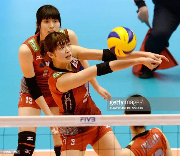 Saori Kimura of Japan receives the ball near Risa Shinnabe and Nana Iwasaka during their FIVB volleyball women's Grand Champions Cup match against...