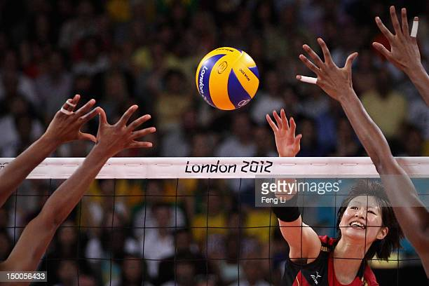 Saori Kimura of Japan spikes the ball as Fernanda Rodrigues and Thaisa Menezes of Brazil defend during the Women's Volleyball semifinal match on Day...