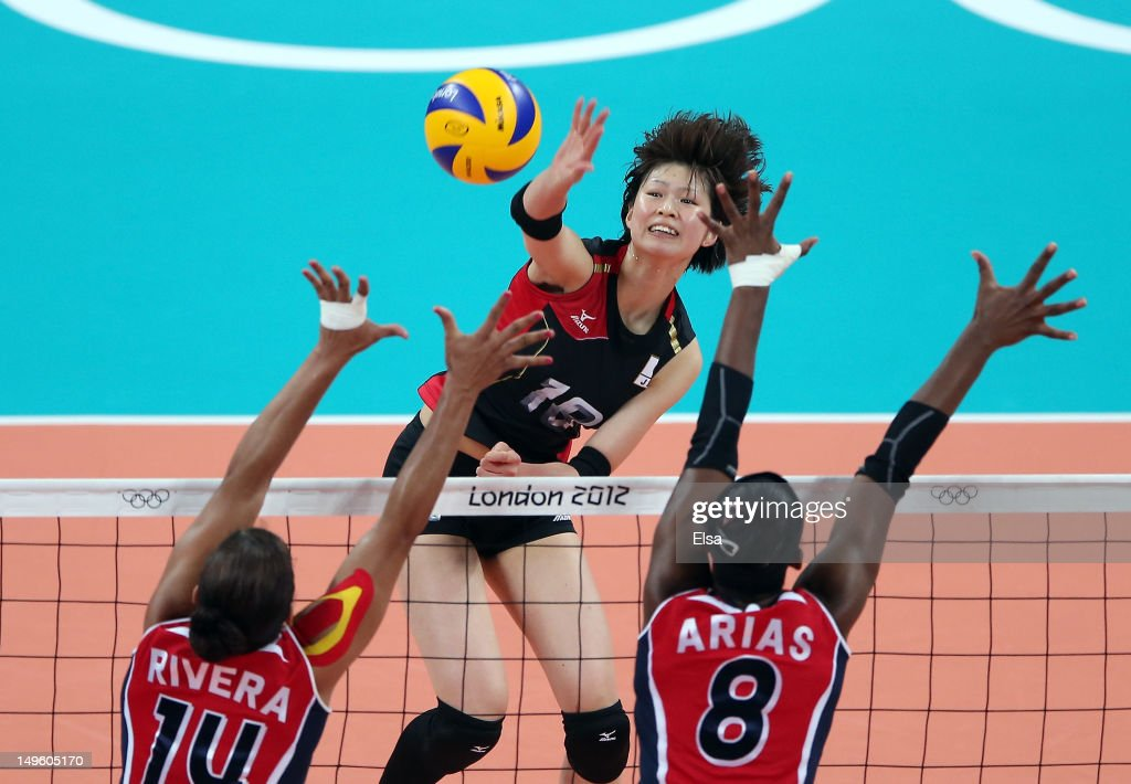 Saori Kimura #18 of Japan spikes the ball as Prisilla Altagracia Rivera Brens #14 and Candida Estefany Arias Perez #8 of Dominican Republic defend during Women's Volleyball on Day 5 of the London 2012 Olympic Games at Earls Court on August 1, 2012 in London, England.