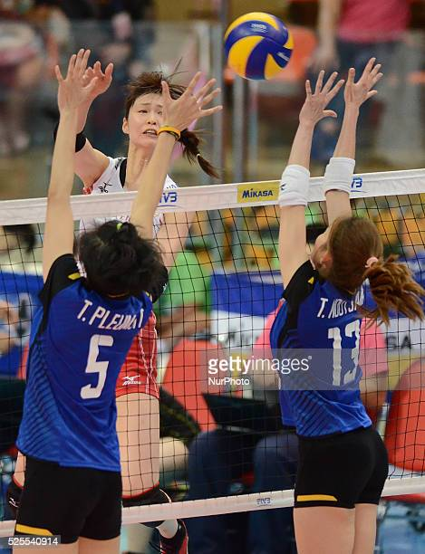 Saori Kimura of Japan spikes the ball as Thailand players attemp to block during their FIVB World Grand Prix intercontinental round match at Indoor...