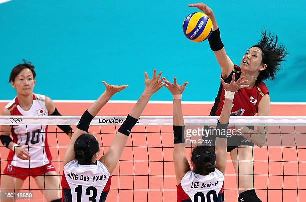 Saori Sakoda of Japan spikes the ball against DaeYoung Jung and SookJa Lee of Korea during the Women's Volleyball on Day 15 of the London 2012...
