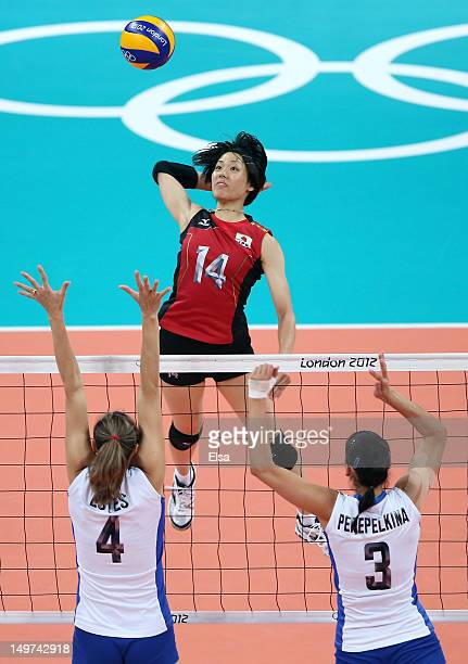 Saori Sakoda of Japan spikes the ball as Evgenia Estes and Maria Perepelkina of Russia defend during Women's Volleyball on Day 7 of the London 2012...