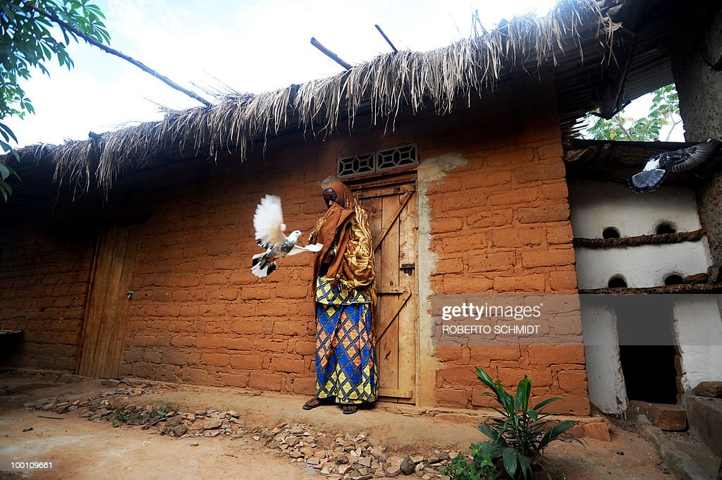 AUSSEILL -- Saphia Bizimana, stands in front of a brick building she had built with her own money next to a house which was given to her and her family by the United Nations in a 'Peace Village' ne...