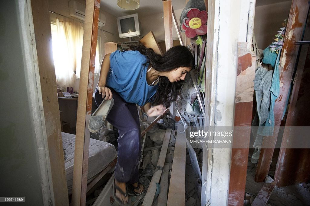 Sapir Hakmon retrieves one of her shoes from her damaged home after it was hit by a rocket launched by Palestinian militants from the Gaza Strip in the southern Israeli city of Beer Sheva on November 20, 2012. Israel put on hold its threatened Gaza ground offensive to give Egyptian-led truce talks a chance as top diplomats flew in to boost efforts to end nearly a week of cross-border violence. AFP PHOTO/MENAHEM KAHANA