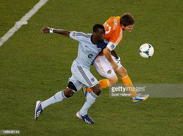 J Sapong of Sporting Kansas City fights for the ball against Bobby Boswell of the Houston Dynamo in the second half at BBVA Compass Stadium on May 12...