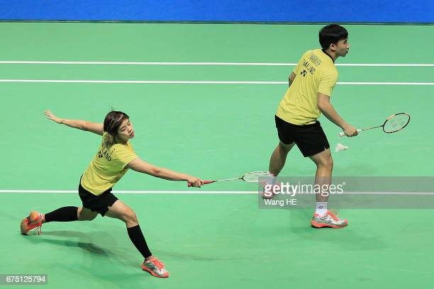 Sapslewiree Taerattan of Thailand hits a return next to her partner Dechapol Puavaranukroh during their mixed doubles final match against Lu Kai and...
