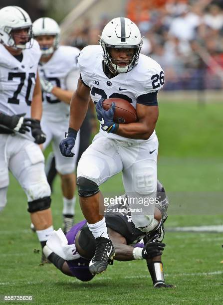 Saquon Barkley of the Penn State Nittany Lions breaks a tackle attempt by Montre Hartage of the Northwestern Wildcats on a 53 yard touchdown run at...