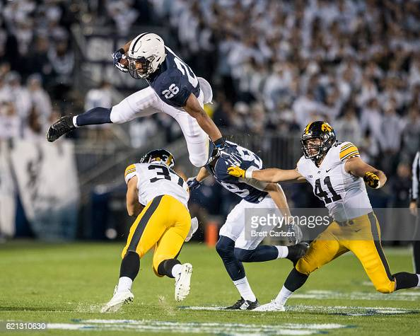 Saquon Barkley of the Penn State Nittany Lions flies over Brandon Snyder of the Iowa Hawkeyes while carrying the ball during the first quarter on...
