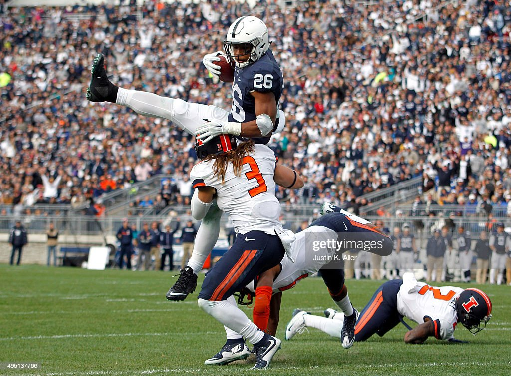 Saquon Barkley #26 of the Penn State Nittany Lions jumps over defenders V'Angelo Bentley #2, Taylor Barton #3 and Eaton Spence #27 of the Illinois Fighting Illini for a 7 yard touchdown run in the fourth quarter during the game on October 31, 2015 at Beaver Stadium in State College, Pennsylvania.